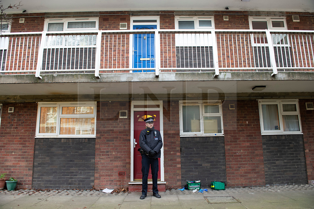 © Licensed to London News Pictures. 02/01/2019. Greenwich, UK. Police officer stands outside a ground floor flat. A man in his 30s is in a critical condition after a stabbing in Greenwich. The man was found with stab wounds to his stomach this morning. Police are on guard at a flat and first aid gloves are still on the ground outside the flat.Photo credit: Grant Falvey/LNP