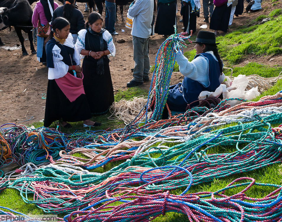 At the Saturday animal market, a woman sells rope in Otavalo, Ecuador, South America. The culturally vibrant town of Otavalo attracts many tourists to a valley of the Imbabura Province of Ecuador, surrounded by the peaks of Imbabura 4,610m, Cotacachi 4,995m, and Mojanda volcanoes. The indigenous Otavaleños are famous for weaving textiles, usually made of wool, which are sold at the famous Saturday market and smaller markets during the rest of the week. The Plaza del Ponchos and many shops tantalize buyers with a wide array of handicrafts. Nearby villages and towns are also famous for particular crafts: Cotacachi, the center of Ecuador's leather industry, is known for its polished calf skins; and San Antonio specializes in wood carving of statues, picture frames and furniture. Otavaliña women traditionally wear distinctive white embroidered blouses, with flared lace sleeves, and black or dark over skirts, with cream or white under skirts. Long hair is tied back with a 3cm band of woven multi colored material, often matching the band which is wound several times around their waists. They usually have many strings of gold beads around their necks, and matching tightly wound long strings of coral beads around each wrist. Men wear white trousers, and dark blue ponchos. Otavalo is also known for its Inca-influenced traditional music (sometimes known as Andean New Age) and musicians who travel around the world.