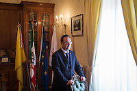 GANGI, ITALY - 30 MAY 2015: Mayor of Gangi Giuseppe Ferrarello poses for a portrait in his office in Gangi, Italy, on May 30th 2015. Gangi is a town with a population of 7,000 between Palermo and Catania, in the centre of Sicily, whose local administration is giving away abandoned houses of the historical centre for free. The Mayor of Gangi Giuseppe Ferrarello conceived the initiative of giving houses for free as a means to diversify the local economy - primarily dependent on agriculture and animal husbandry - by boosting tourism-related activities, and consequently counteract the phenomenon of depopulation that is typical of many small Italian towns where employment possibilities have been on a downward trajectory for years. The renovations of the assigned homes have also given work to local artisans.
