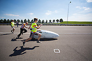 Teamleden begeleiden de VeloX2 tijdens de start. Het Human Power Team Delft en Amsterdam, bestaande uit studenten van de TU Delft en de VU Amsterdam, trainen op de RDW baan in Lelystad voor de laatste keer voor de recordpoging. In september wil het team met Jan Bos en Sebastiaan Bowier het snelheidsrecord op de fiets te verbreken. Dat record staat nu op 133 km/h.<br /> <br /> Team members are guiding the VeloX2 at the start. Human Power Team Delft and Amsterdam are having the last training for the record attempt in Battle Mountain (USA) at the RDW test track in Lelystad. The team will try to break the world speed record with a human powered vehicle with riders Jan Bos and Sebastiaan Bowier. The record is now at 133 km/h..