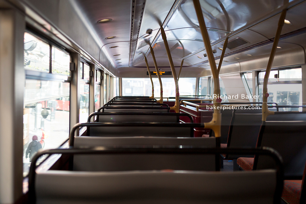 As Londoners are increasingly urged to work from home rather than commute on public transport while the threat to public health increases during the worldwide Coronavirus pandemic, an unusual empty top deck of a Routemaster bus lacks daytime passengers as it drives through London's West End district, on 12th March 2020, in London, England.