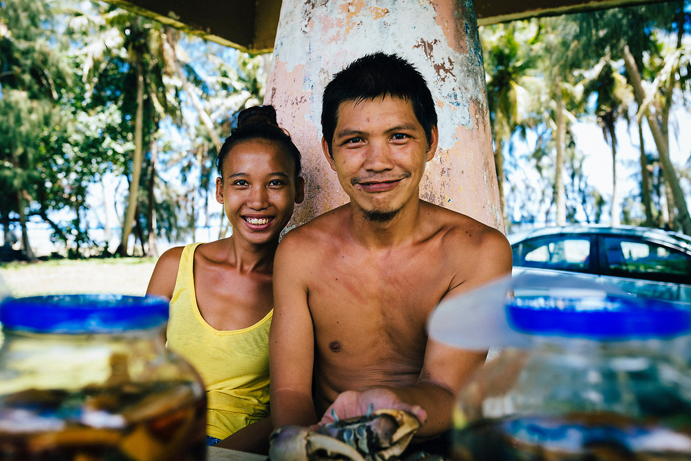 A young couple selling pickled papaya and land crabs along the side of the road in southern Guam.