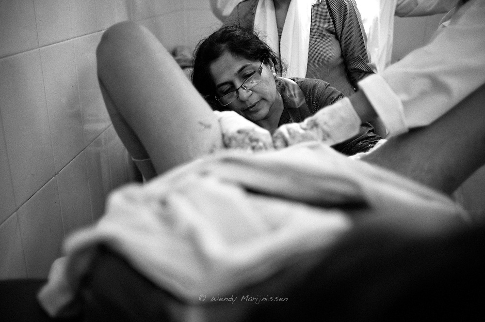 Dr. Musarat tries to stitch up a woman that continued bleeding heavily after her delivery. Most of the maternal deaths occur after giving birth and continued heavy blooding without proper care of skilled staff. Karachi, Pakistan, 2010