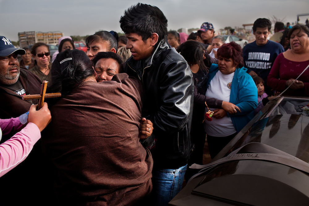 Family members try to restrain a screaming woman at the funeral of two women who were shot at a masacre in Ciudad Juarez that left 13 dead and over a dozen wounded. Most of the victims were between the ages of 14 and 20 years old and were attending a birthday party.
