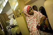 During a two-hour flight to attend the first-ever international Conference on Womens' Challenge in Darfur. Women sit patiently in the cabin of a chartered Russian Antonov aircraft during flight to Al Fasher (also spelled, Al-Fashir) in north Darfur where women from remote parts of Sudan gathered to discuss peace and political issues. The short flight saves them a hazardous five-day drive by road, known for extreme acts of violence by rebels and Janjaweed soldiers.