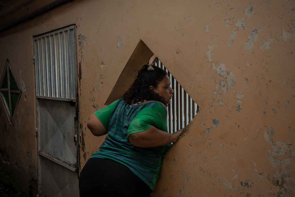 "MARACAY, VENEZUELA - JULY 16, 2016: Evelin RodrÍguez looks out to the street from her home while caring for her two schizophrenic sons, Gerardo and Accel. It is difficult to care for them, because they live in Venezuela - a country suffering from severe shortages of medicines, including the psychiatric drugs that she needs to keep her sons' conditions stabilized. It is an exhausting task taking care of them and going from pharmacy to pharmacy for hours searching for the medicines that her sons need, that she is rarely able to find. She copes by reducing their doses, and by sharing their prescriptions depending on which son needs the medicine the most each day. Evelin is a lawyer, but has quit all of her work since Accel attempted to cut off his arm after three weeks without his medicine. Evelin now spends her days looking after Accel and Gerardo, too afraid to leave them alone because they might hurt themselves.  ""I am tired,"" she said. ""This is too much sometimes"". PHOTO: Meridith Kohut for The New York Times"