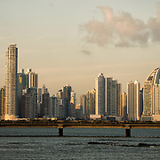 The fading golden glow of the setting sun catches the modern skyscrapers of the skyline of the Punta Paitilla district of Panama City, Panama. In the foreground is the controversial Coastal Beltway (Cinta Costera III) that runs around Casco Viejo.