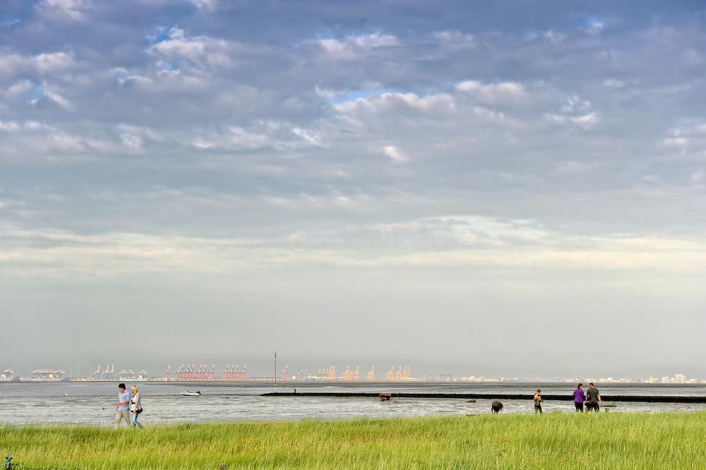 An der Nordseeküste von Burhave in Richtung Bremerhaven. Am Horizont sieht man die Kräne des Hafens.