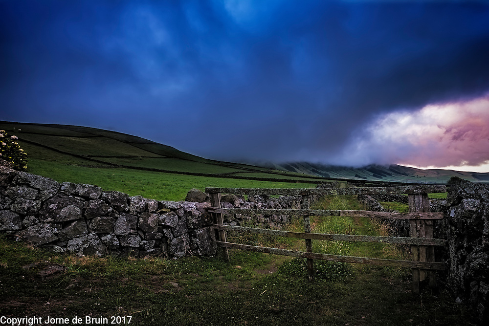 Farmfield divided by onld stone walls underneath a brodding sunset sky. Terceira, Azores, Portugal.