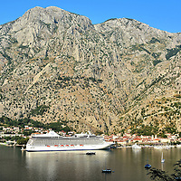Cruise Ship Docked at Bay of Kotor in Kotor, Montenegro <br /> Kotor is a small, fortified city tucked into the base of Mount Lovćen along a submerged river valley called Boka Kotorska. Its origin dates back to antiquity. Old Town's charm reflects when it was a Venetian Republic province from 1420 until 1797. Kotor has become a popular port for cruise ships sailing through the Mediterranean and the Adriatic Sea.