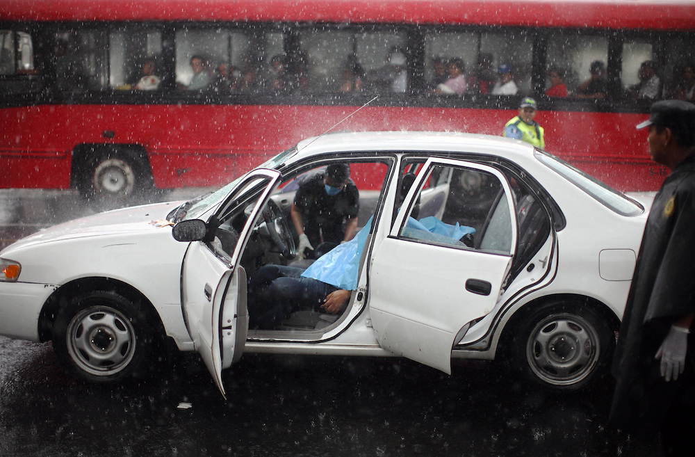 A man murdered by unknown people laid inside a car as police investigators work in the crime scene, Guatemala City, Tuesday, June 16, 2009. (AP Photo/Rodrigo Abd)