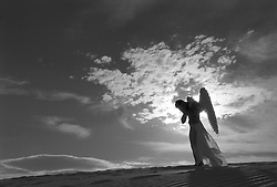 male angel covering his face in a dramatic desert landscape