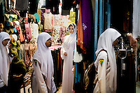 Students walk past a veiled, caucasian looking mannequin in a market in Banda Aceh, Indonesia, Thursday, Nov. 19, 2009. Aceh Province is the only province to enforce Islamic Law in Indonesia, the most populated muslim country in the world.
