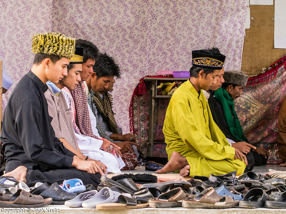 26 OCTOBER 2012 - PULASAIZ, NARATHIWAT, THAILAND:  Men and teenaged boys attend Eid al-Adha services in the mosque in the villiage Pulasaiz, in the province of Narathiwat, Thailand. Eid al-Adha, also called Feast of the Sacrifice, is an important religious holiday celebrated by Muslims worldwide to honor the willingness of the prophet Ibrahim (Abraham) to sacrifice his firstborn son Ishmael as an act of submission to God, and his son's acceptance of the sacrifice before God intervened to provide Abraham with a ram to sacrifice instead. In 2012 Eid al-Adha was celebrated Oct 25 - 26.    PHOTO BY JACK KURTZ