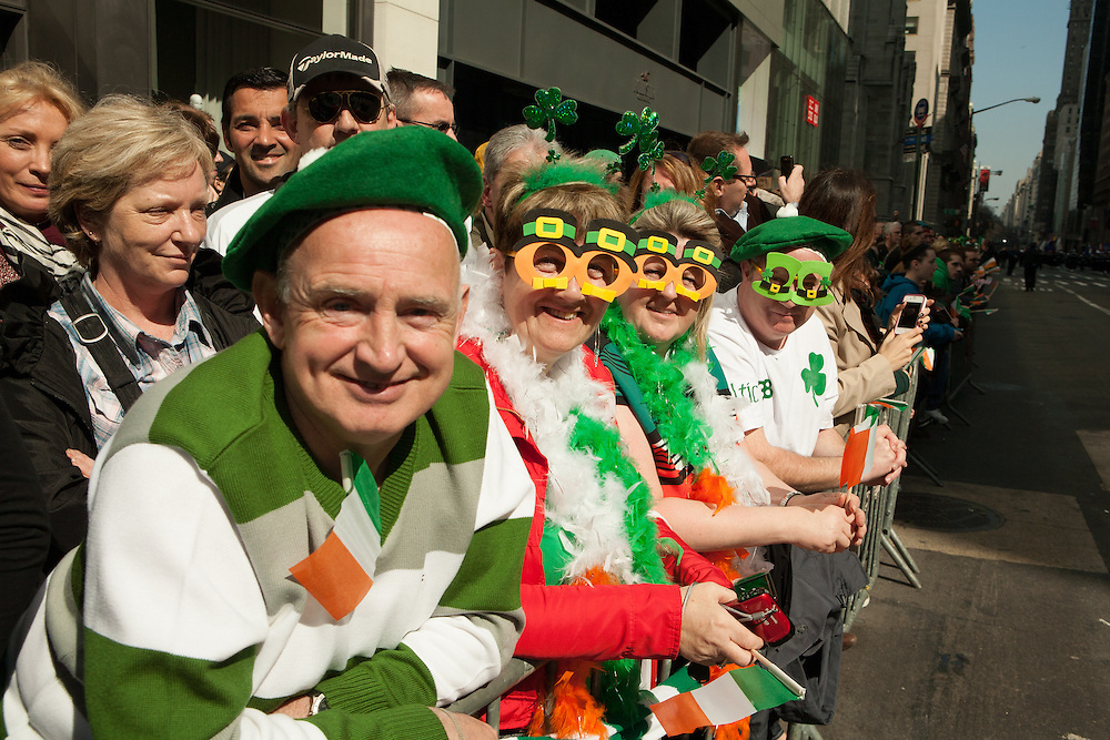 People in leprechaun glasses watching the parade.