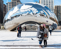 "© Licensed to London News Pictures. 15/12/2016. Chicago, USA. The city of Chicago suffers the first severe cold of the year with daytime temperatures of -5F or -15C recorded.  Tourists continue to brave the low temperatures to visit some of the city's iconic landmarks, such as Cloud Gate (""The Bean"").   Photo credit : Stephen Chung/LNP"
