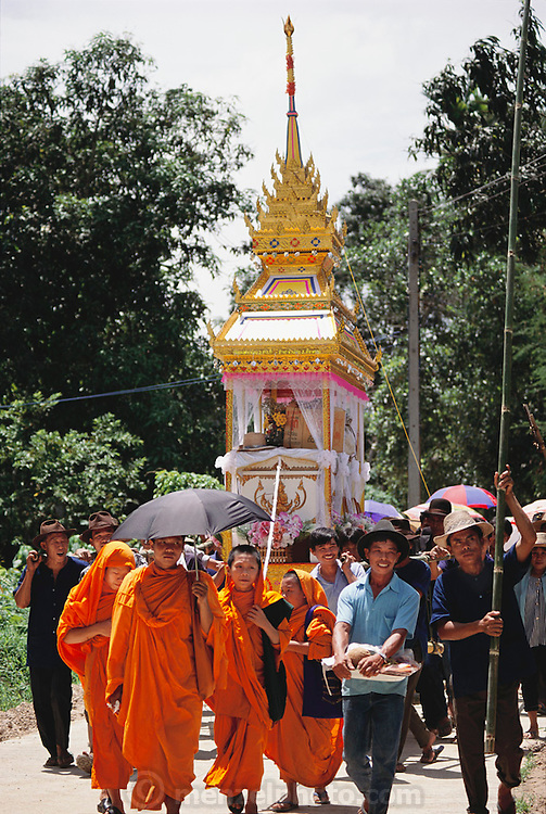 After the death of a 72-year old man who lived across the road from the Khuenkaew family compound, his family followed Thai tradition and bought a castle-like, wood-and-crepe paper funeral bier and placed the body on top. Then the village held a two-day wake, complete with tents, music, gambling, and outdoor barbecues. Gifts were piled atop the casket. Afterward, the men carried the bier on long bamboo poles to the cemetery. The family posed for photographs in front of the bier, said good-bye to the dead man, and left the cemetary-keeper to burn the remains. Funeral. Material World Project.