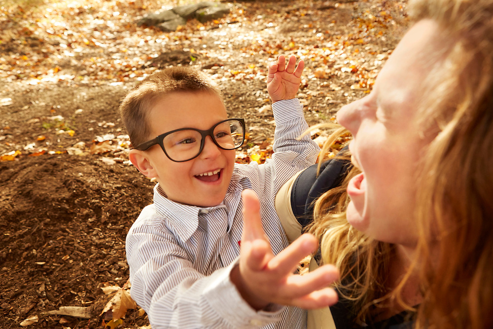 Lifestyle photograph of boy wearing glasses having fun and playing with mother in park during Autumn