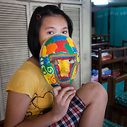 """Kim. (Not her real name). She loves being in the Laura Vicuna home because of the importance given by the Sisters. She loves reading books and wants to be a dentist. """"My mask represents what I want in life - to be happy and to have a colourful life."""""""