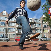 Nederland Rotterdam 01-10-2009 20091001 Foto: David Rozing Achterstandswijk Crooswijk. Allochtone jongen speelt op voetbalveldje, houdt een balletje hoog. Boy playing soccer in Crooswijk, deprived area in Rotterdam, nieghbourhood.                                                       .Foto: David Rozing