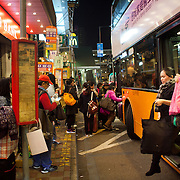 Filipino women get off and on public transport in Hong Kong Central on a Sunday evening. Hong Kong has a huge Filipino population, most of them women working as domestic servants. They meet in public on their days off since none of them have their own private accomodation. 7 million people live on 1,104km square, making it Hong Kong the most vertical city in the world.