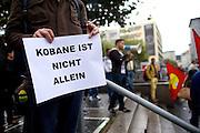 Frankfurt am Main | 08 Oct 2014<br /> <br /> Am Mittwoch (08.10.2014) nahmen an der Konstablerwache in der Innenstadt von Frankfurt am Main etwa 100 Menschen an einer Kundgebung f&uuml;r Solidarit&auml;t mit der von IS (ISIS, ISIL, Islamischer Staat) angegriffenen Stadt Kobane (auch: Ain al-Arab) teil. Die kundgebung verlief friedlich, es kam nur zu einer kleinen St&ouml;rung durch einen jungen Moslem, der sich durch einen Redebeitrag in seinem Glauben beleidigt f&uuml;hlte.<br /> Hier: Ein Mann mit einem Transparent mit der Aufschrift &quot;Kobane ist nicht allein&quot;.<br /> <br /> &copy;peter-juelich.com<br /> <br /> [No Model Release | No Property Release]