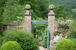 Gate with stone pillars and inscription leading from Well Court towards the Kitchen Garden at Snowshill Manor