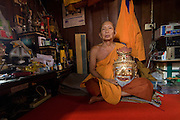The Chief Priest of Wat Kokgate, Phra Phan seated in his room, carrying a traditional mask.