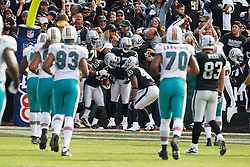 November 28, 2010; Oakland, CA, USA;  Oakland Raiders wide receiver Jacoby Ford (12) celebrates with teammates after returning the opening kick off 100 yards for a touchdown against the Miami Dolphins during the first quarter at Oakland-Alameda County Coliseum.