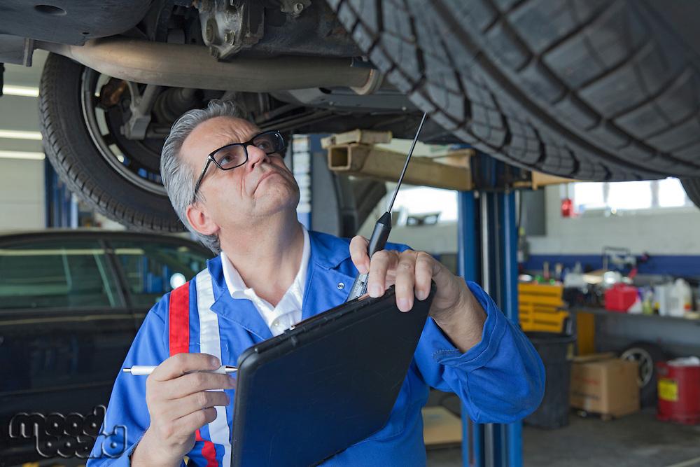 Mechanic analyzing car engine at auto repair shop