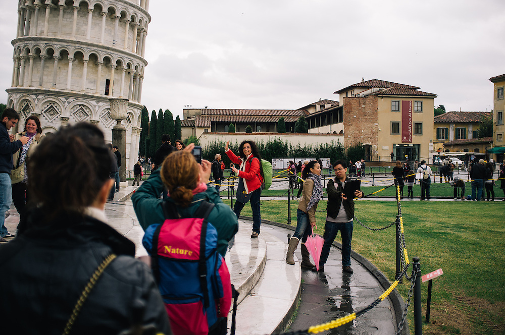 Tourists having their photos taken at he leaning tower of Pisa in the Piazza del Duomo, Italy