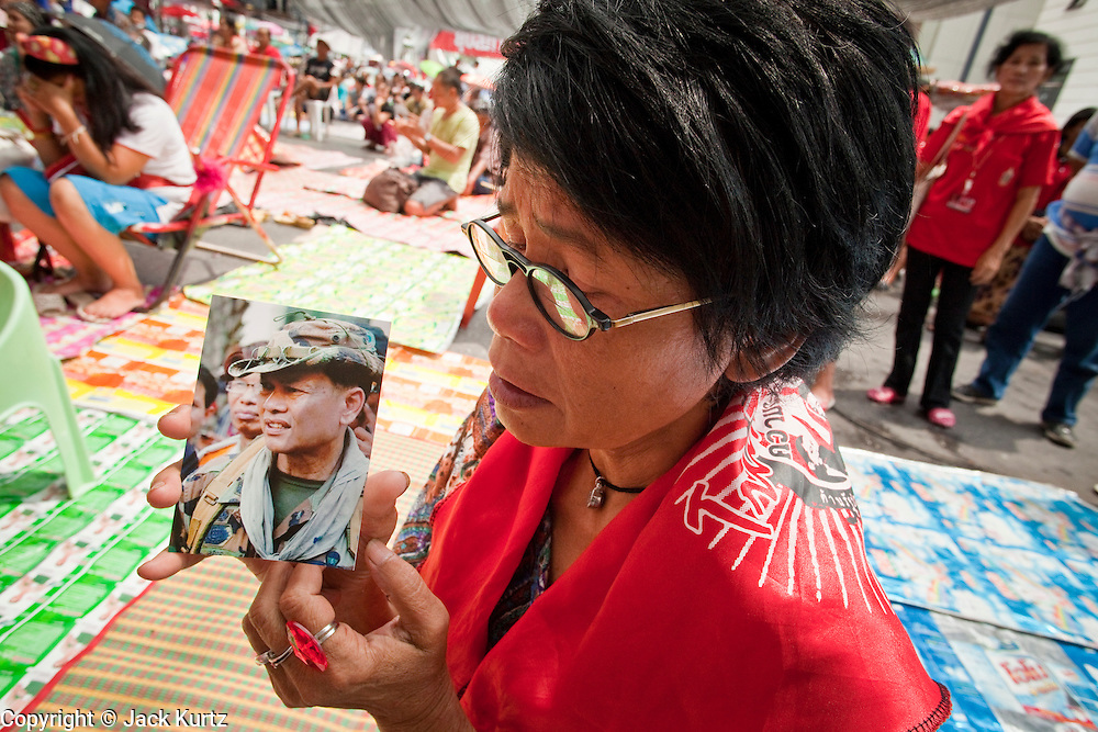 "17 MAY 2010 - BANGKOK, THAILAND: A woman with a photo of Seh Daeng, the Red Shirts' unofficial military commander, cried upon hearing of Seh Daeng's death Monday. The Thai government announced Monday that renegade army general and the Red Shirts unofficial military commander and staunch supporter, Thai Army Maj. Gen. KHATTIYA ""Seh Daeng"" SAWASDIPOL, died Monday from wounds he suffered when a sniper shot him in the head on May 12 while he was being interviewed by an American reporter. When the announcement was read to the Red Shirt protesters still camped out in Ratchaprasong intersection in Bangkok many started weeping.   PHOTO BY JACK KURTZ"