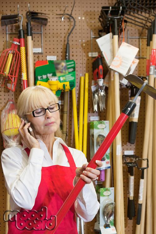 Senior female employee holding gardening tool while using mobile phone