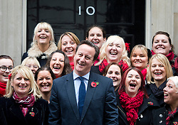 © Ben Cawthra. 10/11/2012. London, UK. British Prime Minister David Cameron poses in front of 10 Downing Street with members of the Military Wives Choir who performed on Downing Street before members of the Royal Marines from Commando 999 (Royal Marines who serve with the UK emergency services) took part in a  speed march for charity around London to raise funds for wounded service personnel. The event takes place on Remembrance weekend. Photo credit: Ben Cawthra