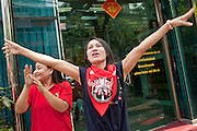"Mar. 27, 2010 - BANGKOK, THAILAND:  Women who work in a jewelry store cheer for Red Shirt protestors in front of their store in Bangkok March 27. More than 80,000 members of the United Front of Democracy Against Dictatorship (UDD), also known as the ""Red Shirts"" and their supporters marched through central Bangkok March 27 during a series of protests against and demand the resignation of current Thai Prime Minister Abhisit Vejjajiva and his government. The protest is a continuation of protests the Red Shirts have been holding across Thailand. They support former Prime Minister Thaksin Shinawatra, who was deposed in a coup in 2006 and went into exile rather than go to prison after being convicted on corruption charges. Thaksin is still enormously popular in rural Thailand.    PHOTO BY JACK KURTZ"