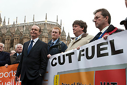 © licensed to London News Pictures. London, UK 07/03/2012. Quentin Wilson poses with members of  the FairFuel protest group hold a banner as they lobby outside the Houses of the Parliaments after handing in their report to Downing Street. Photo credit: Tolga Akmen/LNP