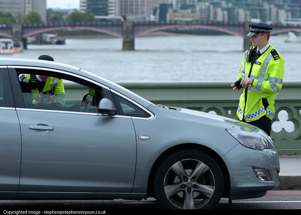© Licensed to London News Pictures. 18/07/2012. Westminster, UK Police stop a car at a security check point on Westminster Bridge. Soldiers, police and security contractors perform security checks around Olympic sites in Westminster today, 18th July 2012. Photo credit : Stephen Simpson/LNP