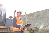 Engineer looking away while holding clipboard at construction site