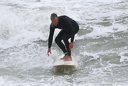 © Licensed to London News Pictures. 29/05/2015. Brighton, UK. A man is surfing while high waves and power gusts of wind are battering Brighton Seafront, today May 29th 2015. Photo credit : Hugo Michiels/LNP