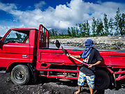 21 JANUARY 2018 - DARAGA, ALBAY, PHILIPPINES: A man loads a truck with sand and gravel from a riverbed. The Mayon volcano is in the background. Mayon volcano, the most active volcano in the Philippines.  More than 30,000 people have been evacuated from communities on the near the Mayon volcano in Albay province in the Philippines. Most of the evacuees are staying at schools in communities outside of the evacuation zone.    PHOTO BY JACK KURTZ