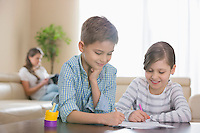 Siblings drawing together at table with mother in background