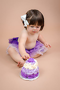 Toddler in purple tutu with cake.