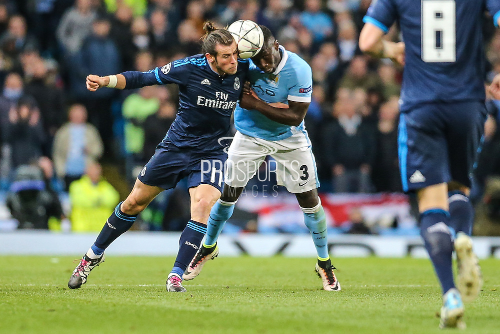 Manchester City's Bacary Sagna and Real Madrid's Gareth Bale go heads in for the ball during the Champions League match between Manchester City and Real Madrid at the Etihad Stadium, Manchester, England on 26 April 2016. Photo by Shane Healey.