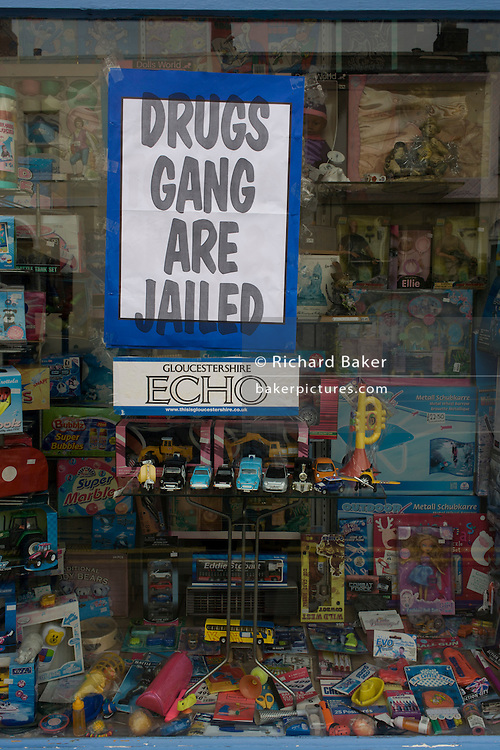 Local newspaper headline with news of a drugs gang jailing verdict in a Cheltenham toyshop window, Gloucestershire, England.
