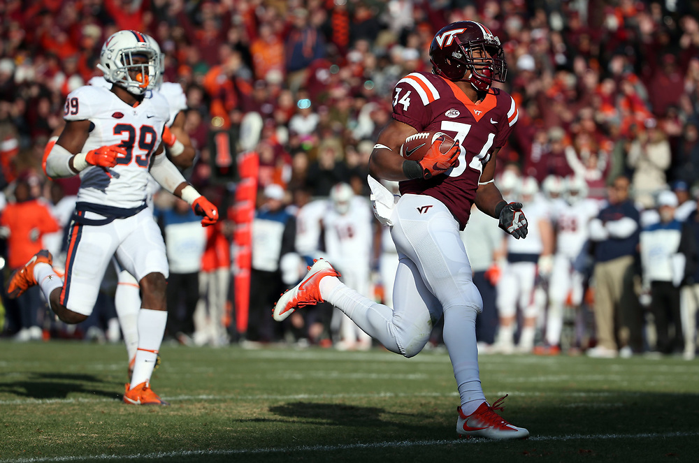 Nov 26, 2016; Blacksburg, VA, USA;  Virginia Tech Hokies running back Travon McMillian (34) scores a touchdown during the third quarter against Virginia Cavaliers defensive back Chris Moore (39) at Lane Stadium. Mandatory Credit: Peter Casey-USA TODAY Sports