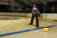 Polly Doucet throws a stone for the yellow team during Gilford Parks and Rec Curling Night at the Arthur Tilton Ice Rink Thursday evening.  (Karen Bobotas/for the Laconia Daily Sun)