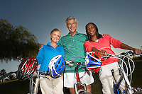 Seniors on bicycles holding cycling helmets at dusk, portrait