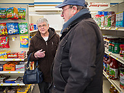 """25 FEBRUARY 2020 - BUTTERFIELD, MINNESOTA: MARY SCHULTE and KERMIT LEET, both from Butterfield, chat at the True Value Hardware Store in Butterfield, MN, a farming community of about 500 people 130 miles southwest of the Twin Cities. The town has been a """"food desert"""" for 10 years after its only grocery store closed in 2010. Barb Mathistad Warner and Mark Warner purchased the True Value store in Butterfield in December, 2018 and started selling groceries in the store in May, 2019. For residents of Butterfield going to a grocery store meant driving 10 miles to St. James, MN, or 20 miles to Windom, MN, the two nearest communities with grocery stores. The USDA defines rural food deserts as having at least 500 people in a census tract living 10 miles from a large grocery store or supermarket. There is a convenience store in Butterfield, but it sells mostly heavily processed, unhealthy snack foods that are high in fat, sugar, and salt.    PHOTO BY JACK KURTZ"""