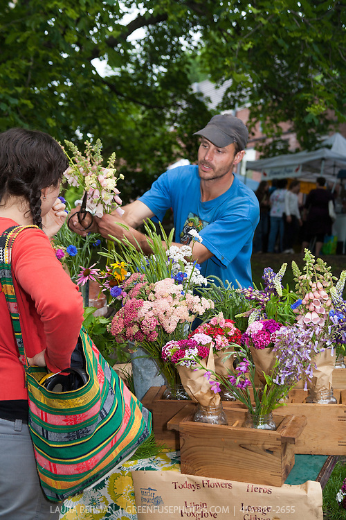 A flower grower selling a bouquet of flowers at a farmers market.