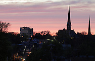 Middletown, New York - Sunset colors the clouds behind steeples and buildings at twilight on April 18, 2012.